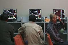 Инвесторы в брокерской конторе в Шэньяне, провинция Ляонин, 12 мая 2014 года. Азиатские фондовые рынки, кроме Японии, снизились во вторник под влиянием отдельных отраслей и локальных факторов. REUTERS/Stringer