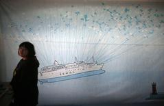 A woman stands in front of a giant banner depicting capsized passenger ship Sewol during a candlelight vigil in Ansan, April 24, 2014. REUTERS/Kim Hong-Ji