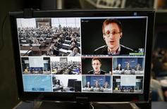 """El ex contratista de la agencia de seguridad de Estados Unidos Edward Snowden aparece en una pantalla mientras participa de una videoconferencia con miembros de la Comisión de Asuntos Legales y Derechos Humanos de la Asamblea Parlamentaria del Consejo de Europa en Estrasburgo. 9 de abril, 2014. El ex contratista de la agencia de Estados Unidos Edward Snowden, quien filtró detalles de un enorme programa de recolección de inteligencia de su país, dijo en una entrevista con la televisión estadounidense que se """"le entrenó como un espía"""" y había trabajado encubierto para agencias de Washington. REUTERS/Vincent Kessler"""