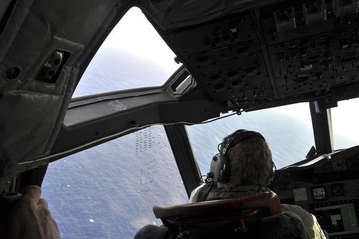 A crew member sits in the cockpit of a Royal New Zealand Air Force (RNZAF) AP-3C Orion maritime patrol aircraft as it continues searching in the southern Indian Ocean for the missing Malaysian Airlines flight MH370, in this picture taken April 1, 2014.  2014.   REUTERS/Kim Christian/Pool