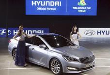 Models pose for photographs with Hyundai Motor Co's New sedan The AG at Busan International Motor Show 2014 in Busan May 29, 2014.  REUTERS/Jo Jung-ho/Yonhap