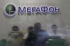 Посетители и персонал в магазине Мегафона в Москве 28 ноября 2012 года. Второй по доле рынка телекоммуникационный оператор России Мегафон в первом квартале 2014 года сократил чистую прибыль на 43 процента в годовом выражении до 7,2 миллиарда рублей из-за амортизационных отчислений, связанных с покупкой оператора Скартел, и убытков от курсовых разниц, сообщила компания в четверг. REUTERS/Sergei Karpukhin