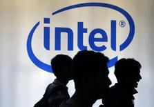 Люди проходят мимо логотипа Intel на выставке Digital Imaging в Джакарте 5 марта 2014 года. Американская Intel Corp представила ходящего и говорящего робота из распечатанных на 3D-принтере деталей, которого любой желающий сможет самостоятельно собрать за $1.600. REUTERS/Beawiharta