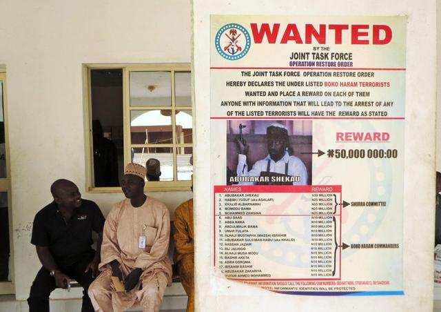 A poster advertising the search for Boko Haram leader Abubakar Shekau and other fighters is pasted on a wall in Baga village on the outskirts of Maiduguri, in the northeastern state of Borno in this May 13, 2013 file photo. REUTERS/Tim Cocks/Files
