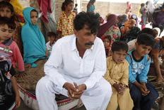 Muhammed Iqbal, 45, husband of the late Farzana Iqbal, sits with his family members at his residence in a village in Moza Sial, west of Lahore May 30, 2014. REUTERS/Mohsin Raza