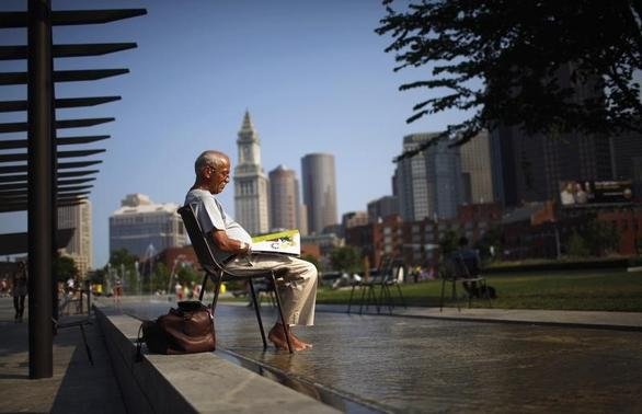 A man soaks his feet in a fountain while reading a magazine on the Rose Kennedy Greenway on a warm summer afternoon in Boston, Massachusetts July 19, 2011. REUTERS-Brian Snyder