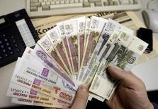 Человек держит в руках рублевые купюры в Санкт-Петербурге 18 декабря 2008 года. Х5 Retail Group договаривается о покупке активов своего крупного экс-франчайзи компании Тамерлан, владеющего около 300 магазинами в Самаре и Волгограде, сообщил представитель Х5. REUTERS/Alexander Demianchuk