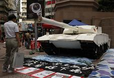 A shopper stands in front of a mock tank made by university students, imitating those used during the military crackdown on the pro-democracy movement at Beijing's Tiananmen Square in 1989, during an exhibition on the movement at Hong Kong's Causeway Bay shopping district June 3, 2014. Wednesday marks the 25th anniversary of the crackdown. REUTERS/Bobby Yip