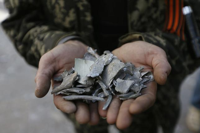A pro-Russian separatist shows shrapnel collected near the site of an explosion in a regional administration building in the eastern Ukrainian city of Luhansk June 3, 2014. REUTERS/Gleb Garanich