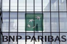 An employee walks behind the logo of BNP Paribas in a company's building in Issy-les-Moulineaux, near Paris, June 2, 2014. REUTERS/Charles Platiau