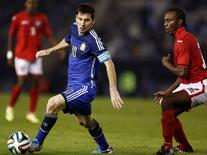 Argentina's Lionel Messi (L) controls the ball in front of Trinindad and Tobago's Yohance Marshall during their friendly soccer match ahead of the World Cup, in Buenos Aires June 4, 2014.   REUTERS/Marcos Brindicci