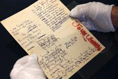 Сотрудник Sotheby's держит в руках написанную рукой Джона Леннона бумагу на аукционе в Нью-Йорке 29 мая 2014 года. Рукописи и рисунки звезды рок-музыки, участника группы The Beatles Джона Леннона, сделанные им в середине 1960-х, были проданы на аукционе Sotheby's за $2,9 миллиона, что вдвое превысило предварительную стоимость лотов, сообщил аукционный дом. REUTERS/Shannon Stapleton