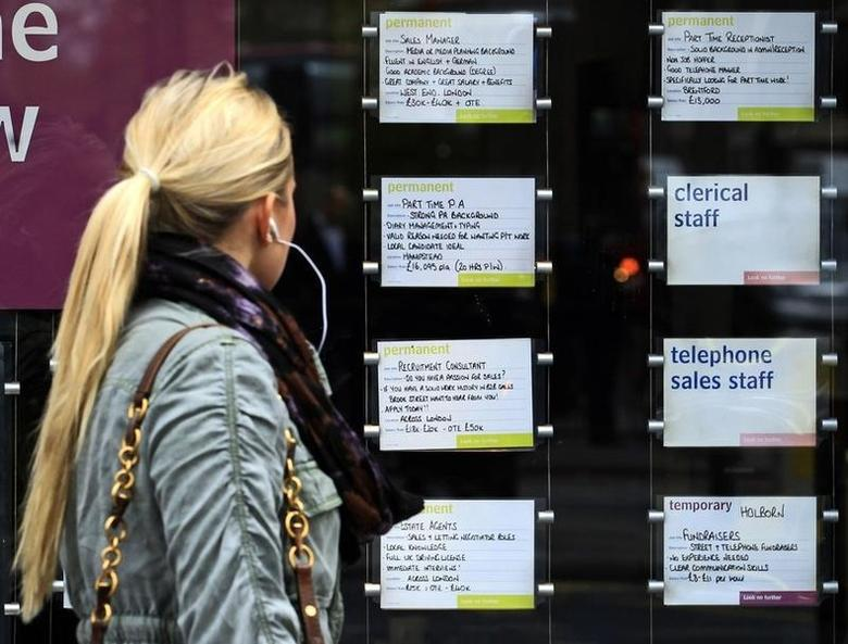 A woman passes notices for jobs in the window of a recruitment agency in London April 13, 2011 FILE PHOTO.    REUTERS/Luke MacGregor