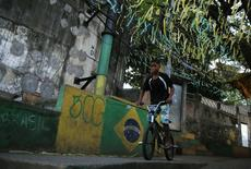 A boy rides his bicycle along a street painted with the Brazilian flag and national colours, at the Turano slum in Rio de Janeiro June 4, 2014. REUTERS/Pilar Olivares