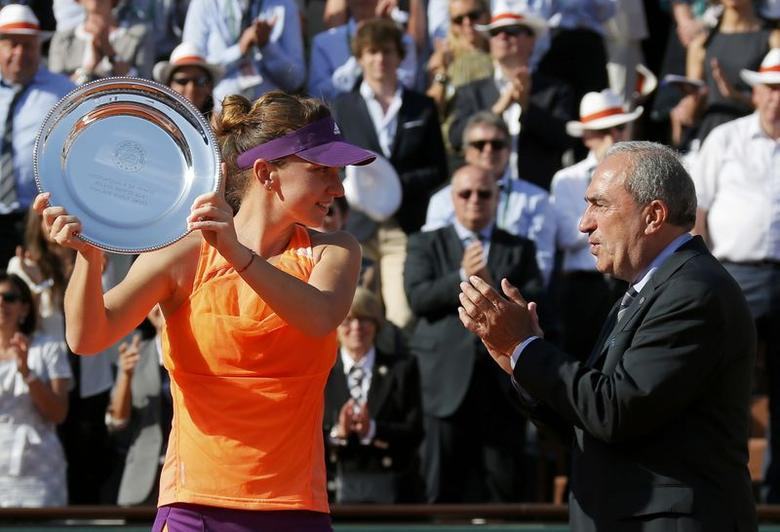 Simona Halep of Romania (L) poses with the trophy as French Tennis Federation (FFT) President Jean Gachassin applauds during the ceremony after being defeated by Maria Sharapova of Russia during their women's singles final match at the French Open tennis tournament at the Roland Garros stadium in Paris June 7, 2014.          REUTERS/Gonzalo Fuentes