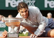 Rafael Nadal of Spain bites the trophy as he poses during the ceremony after defeating Novak Djokovic of Serbia during their men's singles final match to win the French Open Tennis tournament at the Roland Garros stadium in Paris June 8, 2014.                   REUTERS/Jean-Paul Pelissier