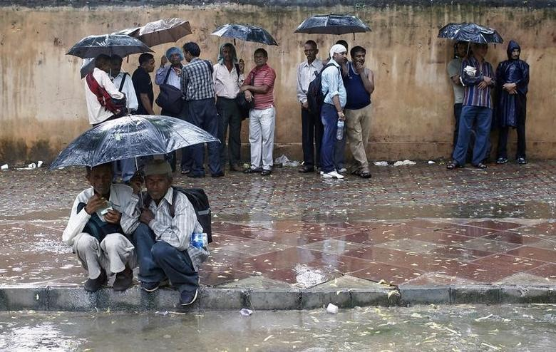 People take shelter under umbrellas during a rain shower in New Delhi August 5, 2013. REUTERS/Anindito Mukherjee/Files