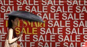 En la imagine, una mujer pasa caminando por una promoción de ventas con descuentso en una tienda en el distrito de Tokyo, 11 de julio de 2011. El crecimiento de Japón en el primer trimestre superó holgadamente las estimaciones iniciales por un aumento inesperado en el gastos de capital, lo que ofrece nuevas señales de que la tercera mayor economía del mundo está en mejores condiciones para resistir una baja del consumo por un alza del impuesto sobre las ventas. REUTERS/Kim Kyung-Hoon