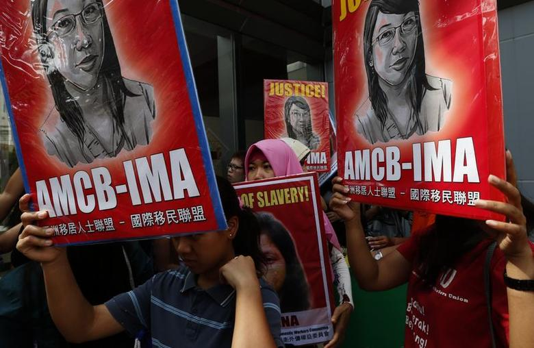 Supporters hold signs with a drawing of Indonesian domestic helper Erwiana Sulistyaningsih, during a protest calling for better protection of migrant workers, outside a magistrate's court in Hong Kong May 20, 2014.   REUTERS/Bobby Yip