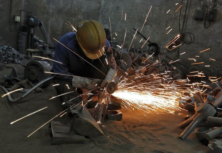 A worker grinds a metal shaft metal used in water pumps at a manufacturing unit on the outskirts of Ahmedabad June 2, 2014. REUTERS/Amit Dave