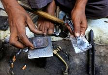 En la imagen un herrero diseña un anillo de oro eb el mercado de Omdurman, 8 de abril de 2014. Los precios del oro subían el martes aunque la firmeza del dólar restaba ímpetu al metal precioso, mientras que el platino extendía su avance por quinta sesión consecutiva en momentos en que colapsaron las negociaciones para resolver una disputa salarial de cinco meses en el mayor productor Sudáfrica. REUTERS/ Mohamed Nureldin Abdallah