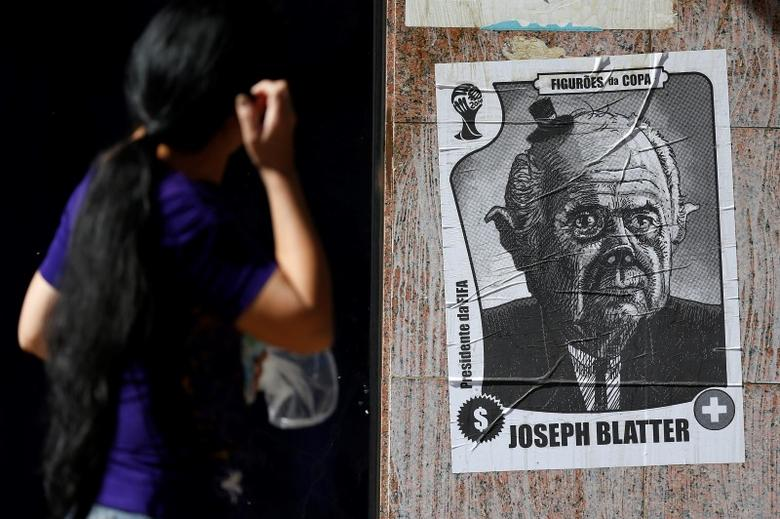 A passerby looks at a poster with a caricature of FIFA President Sepp Blatter in Brasilia, June 10, 2014.  REUTERS/Ueslei Marcelino