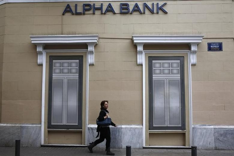 A woman makes her way past the logo of Alpha Bank in Athens March 26, 2014.   REUTERS/Yorgos Karahalis