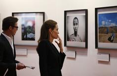 """La actriz Angelina Jolie y su compañero Brad Pitt, miran fotografías de víctimas de violencia en la cumbre de """"Terminar con la Violencia Sexual"""" en Londres, 12 de junio de 2014. Brad Pitt y Angelina Jolie asistieron juntos el jueves a una cumbre global destinada a terminar con la violencia sexual en conflictos, en una muestra del poder de las celebridades, que según el secretario de Asuntos Exteriores de Gran Bretaña William Hague está ayudando a poner foco sobre el problema. REUTERS/Lefteris Pitarakis/Pool"""