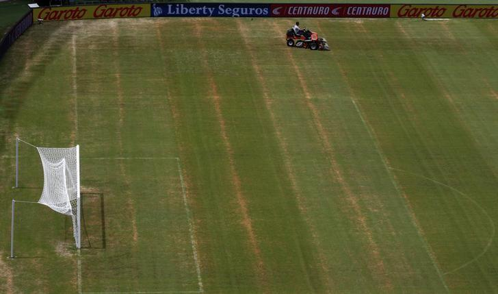 A worker drives a lawn mower on the pitch of the Arena Amazonia stadium in Manaus,June 11 2014.   REUTERS/Siphiwe Sibeko