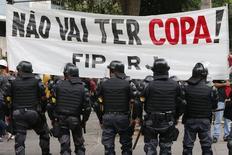 Policiais se posicionam em frente a uma faixa contra a Copa do Mundo durante protesto no Rio de Janeiro, na quinta-feira. 12/06/2014 REUTERS/Marcelo Regua