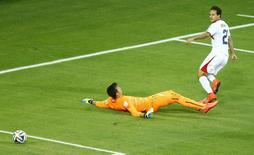 Costa Rica's Marco Urena (in white) scores a goal next to Uruguay's goalkeeper Fernando Muslera during their 2014 World Cup Group D soccer match at the Castelao arena in Fortaleza, June 14, 2014.  REUTERS/Mike Blake