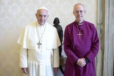 Pope Francis (L) poses with the Archbishop of Canterbury Justin Welby during a private meeting at the Vatican June 16, 2014.  REUTERS/Osservatore Romano