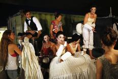 "Cast members wait backstage in between acts during a dress rehearsal of Giuseppe Verdi's opera ""La Traviata"" at the foothill of Masada, an ancient Jewish mountaintop fortress near the Dead Sea in southeast Israel June 10, 2014. REUTERS/Amir Cohen"