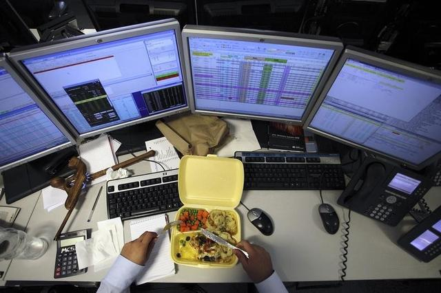 A dealer eats his lunch as he monitors his screens on the trading floor of IG Index in London May 6, 2010. REUTERS/Kevin Coombs