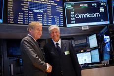 En la imagen, el jefe ejecutivo de Omnicom, John Wren (I), y el CEO de Publicis Group, Maurice Levy (D), se saludan en la bolsa de valores de Nueva York, 29 de julio de 2014. El mercado publicitario global crecerá un 5,4 por ciento este año, hasta 524.000 millones de dólares, ayudado por un incremento en los anuncios de televisión durante el Mundial de fútbol, según la firma encargada de medios Zenith Optimedia. REUTERS/Shannon Stapleton