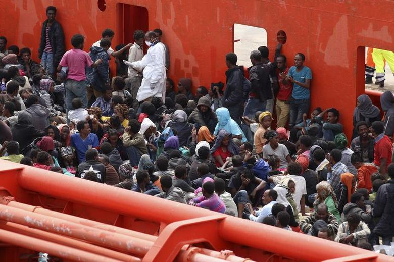 Migrants are seen aboard a navy ship before being disembarked in the Sicilian harbour of Augusta June 1, 2014. REUTERS/Antonio Parrinello