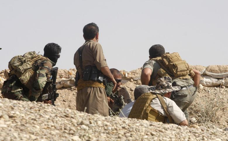 Members of the Kurdish security forces take cover during clashes with militants from the Islamic State of Iraq and the Levant (ISIL) in Jalawla in the Diyala province June 17, 2014.  REUTERS/Stringer