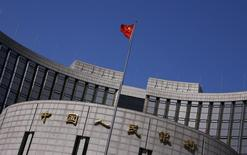 A Chinese national flag flutters outside the headquarters of the People's Bank of China, the Chinese central bank, in Beijing, April 3, 2014. Picture taken April 3, 2014.