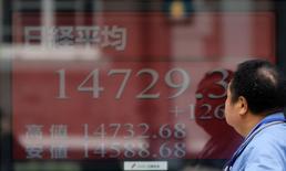 Un hombre mira una pantalla electrónica con los promedios del nikkei japonés en Tokio, 27 de mayo de 2014. Las bolsas de Asia subían el jueves después de que la Reserva Federal de Estados Unidos hizo una evaluación positiva de la economía y se comprometió a mantener una política monetaria acomodaticia. REUTERS/Toru Hanai