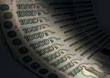 Рублевые купюры в Москве 17 февраля 2014 года. Рубль дорожал в четверг к доллару и бивалютной корзине на фоне тенденций спроса на риск после заседания американского центробанка и перед завтрашней уплатой НДС, а также в преддверии основного для экспортеров налога НДПИ 25 июня. REUTERS/Maxim Shemetov