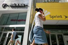 Una mujer habla por teléfono mientras camina frente a tiendas de T-Mobile y Sprint en Nueva York. 30 julio, 2009. Sprint Corp ha conseguido que ocho bancos financien su propuesta de adquisición de T-Mobile US Inc, lo que le acerca más a cerrar un negocio que fusionará al tercer y cuarto operador de telefonía móvil de Estados Unidos, dijeron fuentes cercanas al asunto. REUTERS/Brendan McDermid