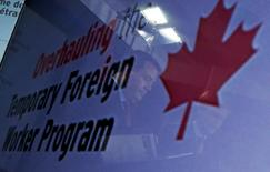 Canada's Employment Minister Jason Kenney is reflected on a screen during a news conference with Immigration Minister Chris Alexander in Ottawa June 20, 2014. REUTERS/Chris Wattie