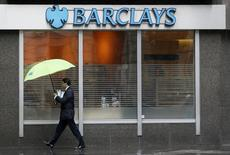 A man shelters under umbrellas as he walks past a Barclays branch in central London May 8, 2014.    REUTERS/Stefan Wermuth