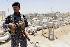 Policier irakien montant la garde dans un champ pétrolier près de Bassorah. Les prix du pétrole, au plus haut depuis neuf mois, occuperont les esprits des investisseurs américains cette semaine à Wall Street, alors que les marchés actions pourraient commencer à réagir au conflit en Irak et aux risques d'approvisionnement en provenance du deuxième producteur de l'Opep. /Photo prise le 18 juin 2014/REUTERS/Essam Al-Sudani