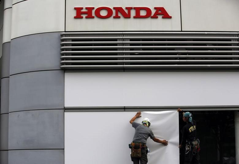Workers stand under the logo of Honda Motor Co. outside the company's headquarters in Tokyo, in this file picture taken October 30, 2013.  REUTERS/Issei Kato/Files/Files