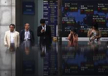 Pedestrians standing in front of an electronic board showing the various countries' stock market indices outside a brokerage are reflected in a polished stone surface, in Tokyo May 13, 2014. REUTERS/Yuya Shino