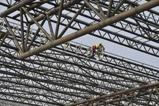 Labourers work at a construction site of a railway station in Hefei, Anhui province, March 28, 2014. REUTERS/Stringer