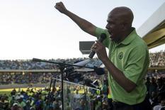"""Президент профсоюза AMCU Джозеф Матунджва выступает на стадионе в Рюстенбурге 23 июня 2014 года. Южноафриканский платиновый профсоюз AMCU сообщил в понедельник, что пятимесячная забастовка """"официально завершена"""", и тысячи шахтеров громогласно одобрили этот шаг, когда лидер профсоюза Джозеф Матунджва спросил, хотят ли они положить конец длиннейшей остановке работы в истории страны. REUTERS/Skyler Reid"""