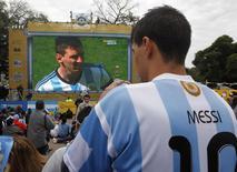 Torcedor com camiseta da argentina de Lionel Messi (telão) durante partida contra o Irã. Foto em Buenos Aires. 21/6/2014 REUTERS/Enrique Marcarian