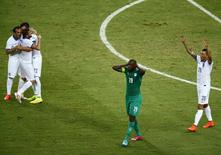 Yaya Toure, da Costa do Marfim, lamenta, enquanto jogadores da Grécia comemoram após partida em Fortaleza. 24/06/2014. REUTERS/Mike Blake